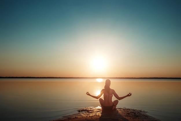 Siluetta della ragazza su un lago e su un bello tramonto