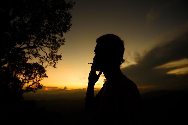 Siluetta della sigaretta di fumo dell'uomo sul tramonto
