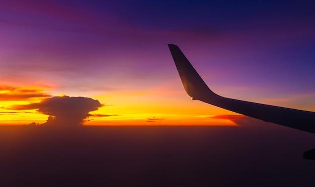 Siluetta della vista dell'ala dell'aeroplano dalla finestra il fondo nuvoloso del cielo di tramonto