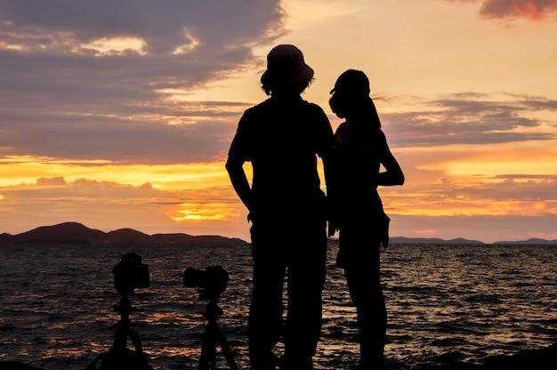 Siluetta delle coppie che si levano in piedi sulla spiaggia al tramonto