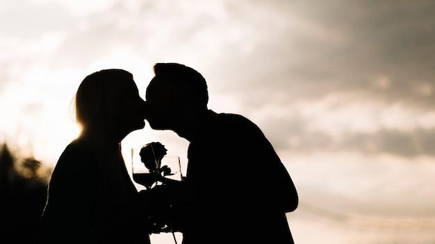 Siluetta delle coppie che tengono bicchiere di vino e rosa che bacia contro il cielo
