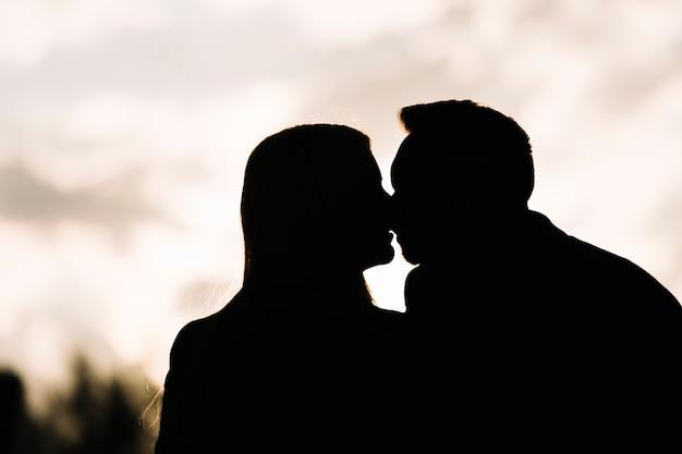 Siluetta delle coppie contro il cielo che si baciano