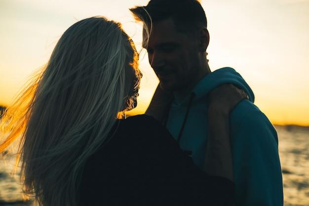 Siluetta delle coppie nell'amore sul pilastro, ora del tramonto