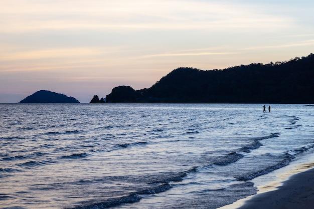 Siluetta delle coppie sopra la superficie dell'onda del mare