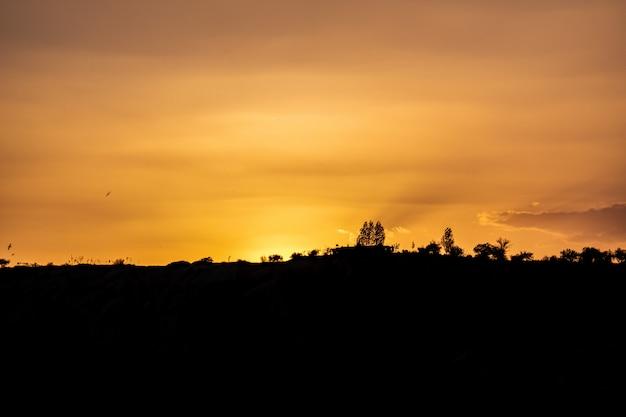 Siluetta delle montagne sotto il bello cielo dorato.