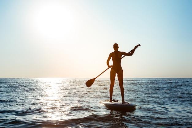 Siluetta di giovane bella donna che pratica il surfing nel mare all'alba.