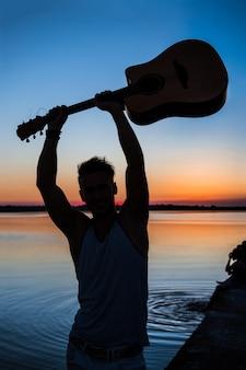 Siluetta di giovane chitarra bella della tenuta dell'uomo alla spiaggia durante l'alba