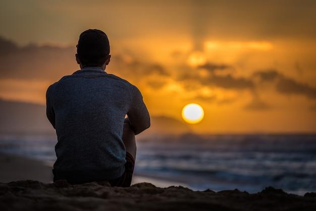 Siluetta di giovane maschio caucasico che si siede sulla spiaggia di tramonto