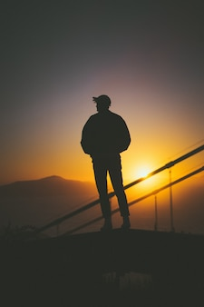 Siluetta di giovane maschio che sta sulla scala dietro i binari della scala con la bella vista di tramonto