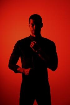 Siluetta di giovane uomo d'affari bello sicuro che porta camicia nera alla luce rossa