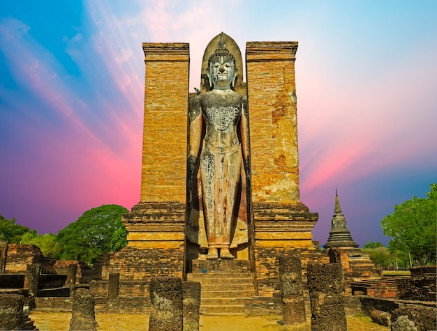Siluetta di grande statua di buddha dentro il tempio di rovina al parco storico di sukhothai
