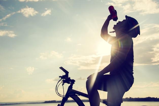Siluetta di riciclaggio dell'acqua potabile e del ciclista al tramonto.