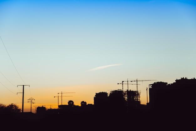 Siluetta di tramonto delle costruzioni in costruzione con le gru dei muratori.