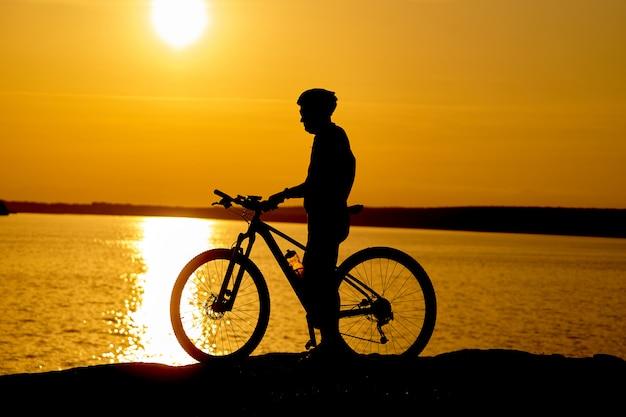 Siluetta di un ciclista maschio con il casco al tramonto vicino al fiume