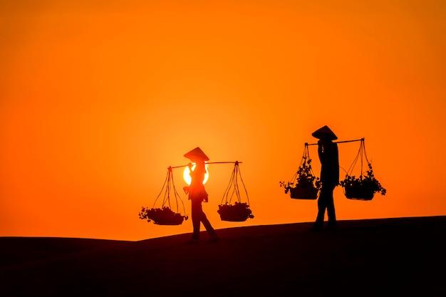 Siluetta di un commerciante di venditore ambulante attraverso il deserto di mui ne nel vietnam