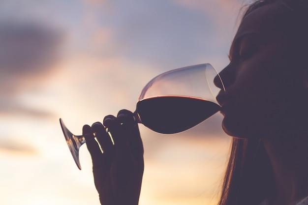 Siluetta di un giovane che si rilassa, che gode e che beve un bicchiere di vino al tramonto di sera.