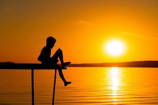 Siluetta di un ragazzo felice che si siede sull'estremità di un ponte sopra il fiume al tramonto