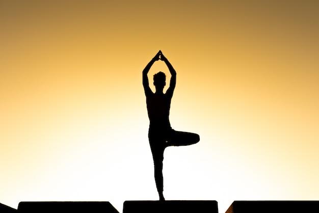 Siluetta di un uomo che pratica l'asana dell'albero di yoga al tramonto, fondo caldo con il testo della copia, concetto di spiritualità.