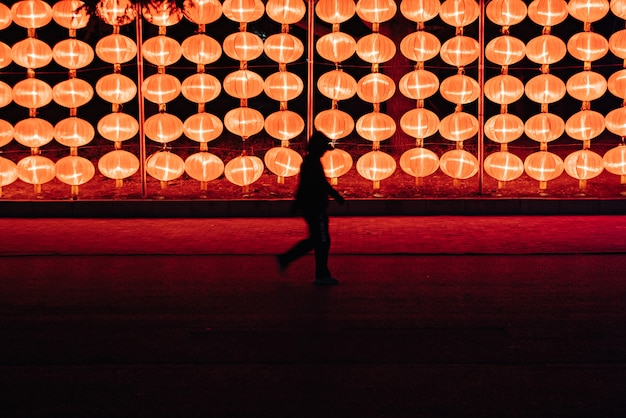 Siluetta di una persona che cammina vicino alle lampade della lanterna al ngiht a dalian, cina di nordest
