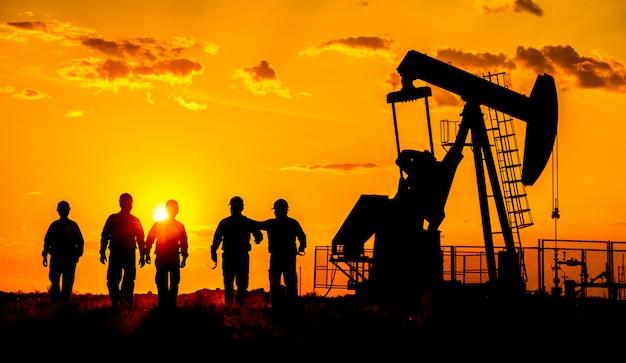 Siluetta di una pompa di petrolio greggio del lavoratore del giacimento di petrolio al tramonto.