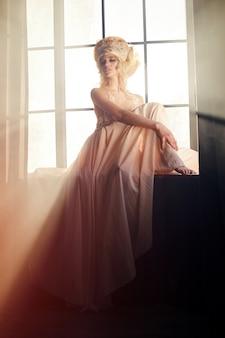 Siluetta di una ragazza sexy della donna vicino al sole di sera della finestra di mattina.