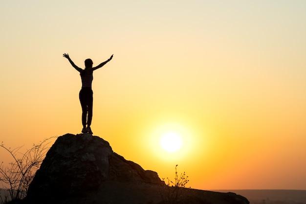 Siluetta di una viandante della donna che sta da solo sulla grande pietra al tramonto in montagne. turista femminile che solleva le sue mani su sull'alta roccia in uguagliando natura. concetto di turismo, viaggi e stile di vita sano.
