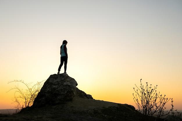Siluetta di una viandante della donna che sta da solo sulla grande pietra al tramonto in montagne. turista femminile su roccia alta nella natura di sera. concetto di turismo, viaggi e stile di vita sano.