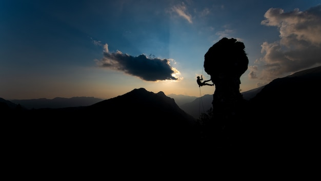 Siluetta di uno scalatore che discende sulla corda dopo la scalata al tramonto
