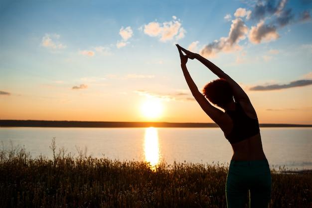 Siluetta di yoga di pratica della ragazza allegra nel campo ad alba.