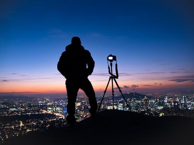 Siluetta diritta dell'uomo dell'ombra su fondo del cielo e del fotografo di alba con una macchina fotografica montata sul treppiede a seoul corea del sud