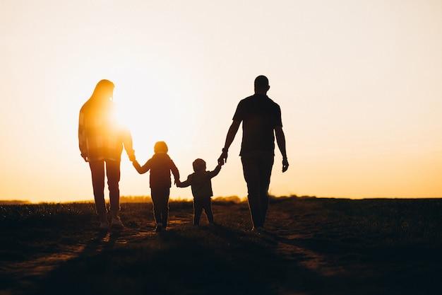 Siluetta felice della famiglia sul tramonto