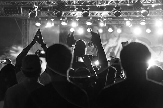 Siluetta in bianco e nero della gente nella folla ad un festival di musica. concerto con persone danzanti in piedi retroilluminate
