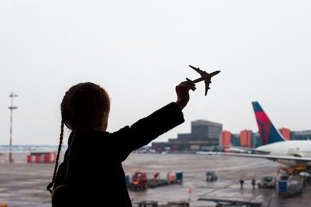 Siluetta nera di un piccolo giocattolo di modello dell'aeroplano sull'aeroporto in mani dei bambini