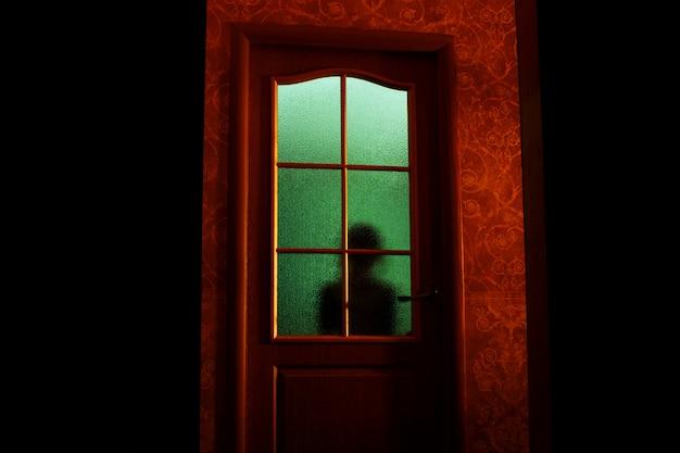 Siluetta scura del bambino dietro il vetro nella luce verde soprannaturale. bloccato da solo nella stanza dietro la porta di halloween. incubo del bambino con alieni, mostri e fantasmi. il male in casa. all'interno della casa stregata.
