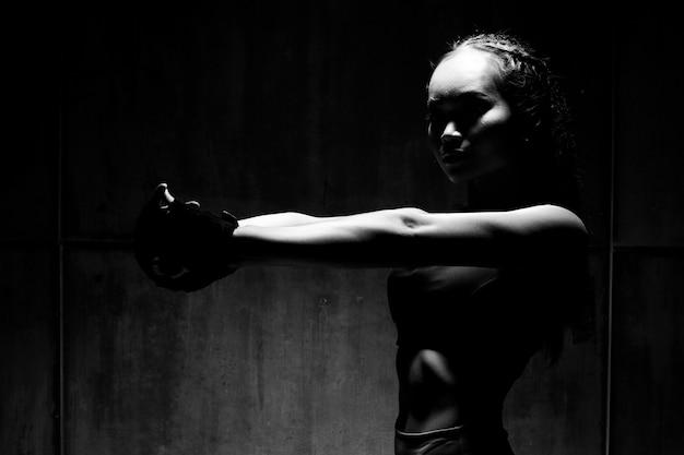 Siluetta scura del punzone del peso di pugilato di esercizio della donna di forma fisica