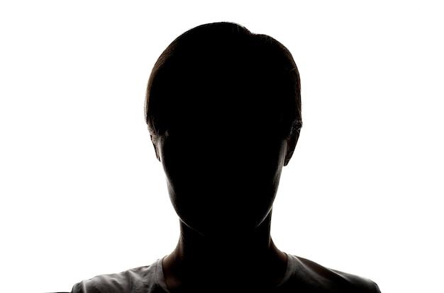 Siluetta scura di una ragazza su una priorità bassa bianca, il concetto di anonimato
