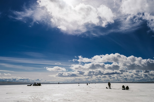 Siluette dei pescatori che pescano e motoslitta in inverno sul ghiaccio