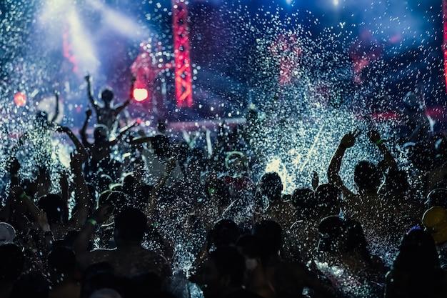 Siluette della folla di concerto davanti alle luci del palcoscenico luminoso, festa in piscina