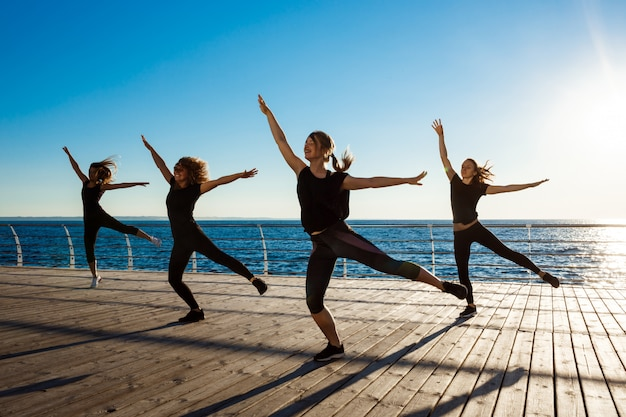Siluette delle donne allegre che ballano zumba vicino al mare all'alba
