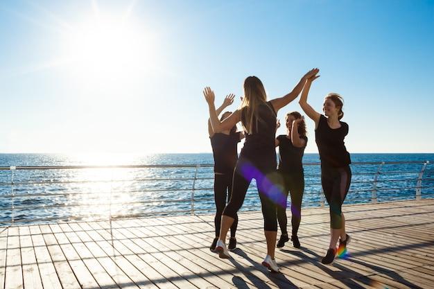 Siluette delle donne allegre che danno highfive vicino al mare all'alba