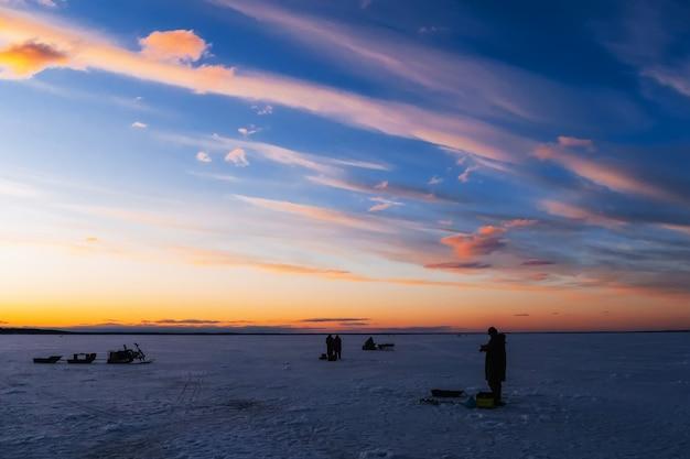 Siluette di un pescatore con una canna da pesca su una pesca invernale