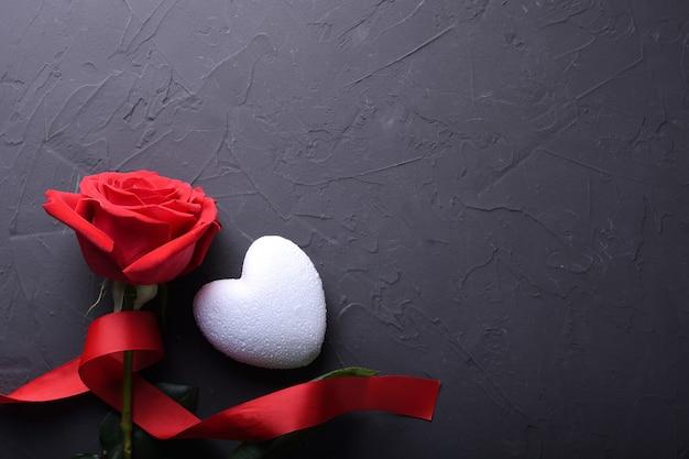 Simboli di amore della cartolina d'auguri del fondo di giorno di biglietti di s. valentino, decorazione rossa con cuore su fondo di pietra. vista dall'alto con spazio di copia e testo. superficie piana