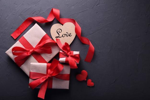 Simboli di amore della cartolina d'auguri del fondo di giorno di biglietti di s. valentino, decorazione rossa con i contenitori di regali su fondo di pietra. vista dall'alto con spazio di copia e testo. superficie piana