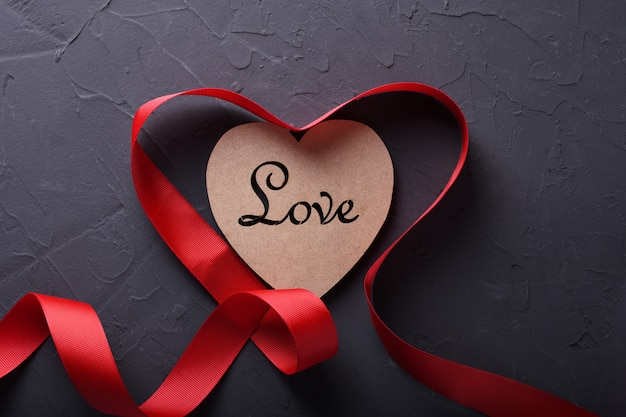 Simboli di amore della cartolina d'auguri del fondo di san valentino, decorazione rossa con cuore su fondo di pietra. vista dall'alto con spazio di copia e testo. superficie piana