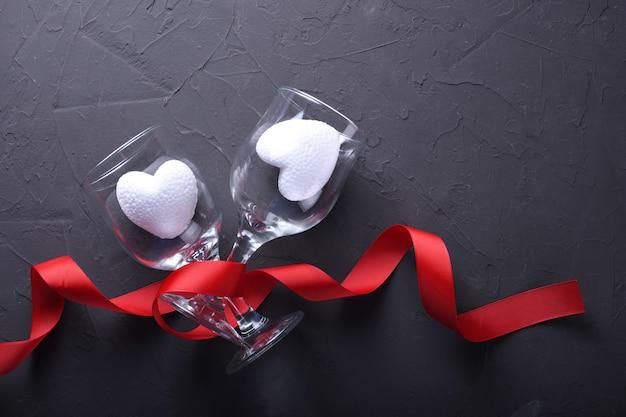 Simboli di amore della cartolina d'auguri del fondo di san valentino, decorazione rossa con i vetri su fondo di pietra. vista dall'alto con spazio di copia e testo. superficie piana