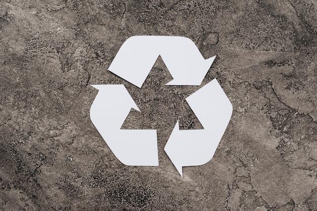 Simbolo bianco di riciclaggio su sfondo sporco