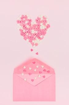 Simbolo del cuore di coriandoli di carta vicino busta