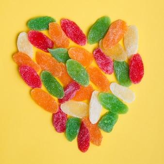 Simbolo del cuore fatto di frutta secca candita su sfondo giallo.