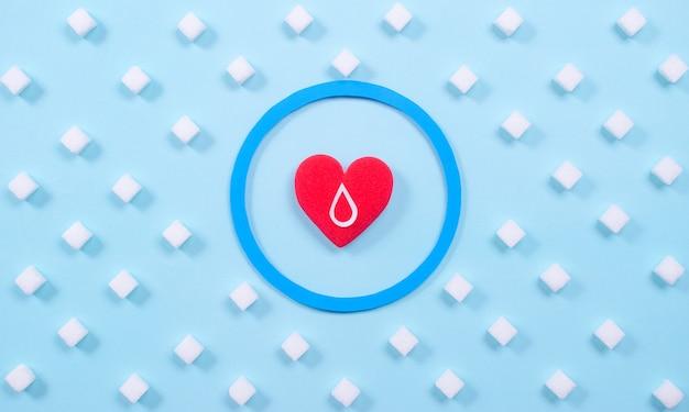 Simbolo del diabete con zolletta di zucchero e cuore rosso su blu pastello. concetto di giornata mondiale del diabete.