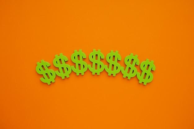 Simbolo del dollaro americano su sfondo arancione. flatlay soldi verdi